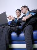 Couples regardant l'ordinateur portatif Photographie stock libre de droits