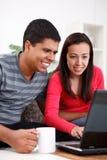 Couples regardant l'ordinateur portatif Photographie stock