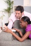 Couples regardant l'ordinateur portatif. Images stock
