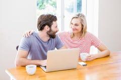 Couples regardant l'un l'autre tout en à l'aide de l'ordinateur portable Image libre de droits