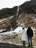 Couples regardant la cascade en Islande image libre de droits
