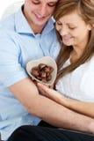 Couples regardant la cuvette en forme de coeur avec du chocolat Photographie stock libre de droits