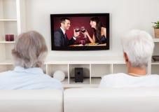 Couples regardant la télévision romantique Image libre de droits