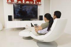 Couples regardant la TV Images libres de droits