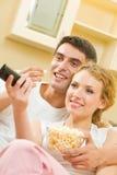 Couples regardant la TV avec le maïs éclaté Photographie stock