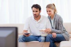 Couples regardant la TV tout en mangeant du maïs éclaté Image stock