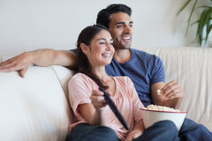 Couples regardant la TV tout en mangeant du maïs éclaté Photo libre de droits