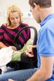 Couples regardant le bébé nouveau-né dans le transporteur Photo stock
