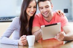Couples regardant le comprimé numérique Images libres de droits