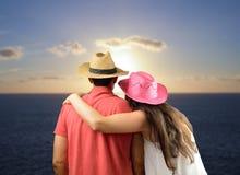 Couples regardant le coucher du soleil sur l'océan Photos libres de droits