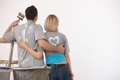 Couples regardant le mur blanc après peinture Photographie stock libre de droits