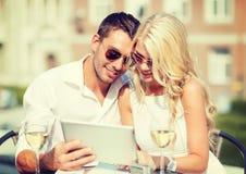 Couples regardant le PC de comprimé en café Image libre de droits
