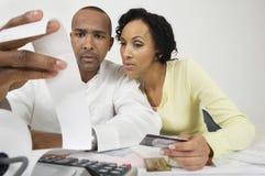 Couples regardant le reçu de dépenses à la maison Photo stock