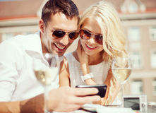 Couples regardant le smartphone en café Photographie stock libre de droits