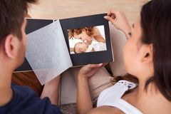 Couples regardant par l'album photos photographie stock libre de droits