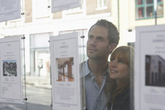 Couples regardant par la fenêtre des agents immobiliers Photo stock