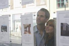 Couples regardant par la fenêtre des agents immobiliers Photo stock