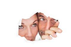 Couples regardant par le papier déchiré Images libres de droits