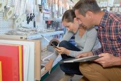 Couples regardant sur la boutique de matériel d'étagère Photos stock