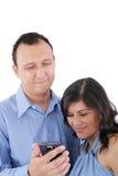 Couples regardant un téléphone portable Images libres de droits