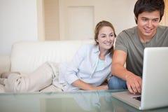 Couples Relaxed utilisant un carnet photos stock