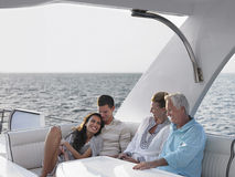 Couples Relaxing On Yacht. Happy young and middle aged couples relaxing on yacht Stock Image
