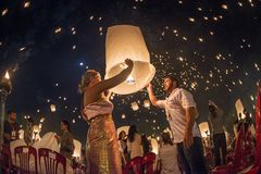 Couples releasing lanterns in the sky during Yi Peng festival, Thailand Stock Image