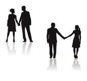 Couples retenant la silhouette de mains Photos stock