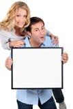Couples retenant le panneau de message blanc Images stock
