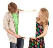 Couples retenant le panneau-réclame blanc, affiche Photographie stock libre de droits