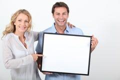 Couples retenant un panneau blanc Images libres de droits