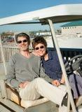 Couples retirés dans le vieux chariot de golf à la plage Images libres de droits