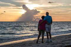 Couples retirés embrassant sur la plage Photo stock