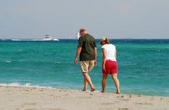 Couples retirés marchant sur la plage Photos libres de droits