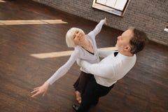 Couples retirés optimistes de danse appréciant la valse dans le studio de danse Images libres de droits