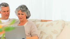 Couples retirés regardant leur ordinateur portatif banque de vidéos