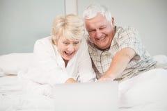 Couples riant tout en à l'aide de l'ordinateur portable dans le lit Images stock