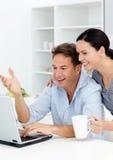 Couples riant tout en loking à l'ordinateur portatif Images stock
