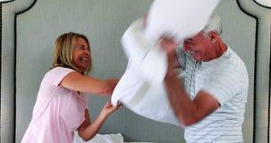 Couples riants ayant le combat d'oreiller sur le lit banque de vidéos