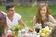 Couples riants ayant un repas ensemble dans le jardin Photographie stock