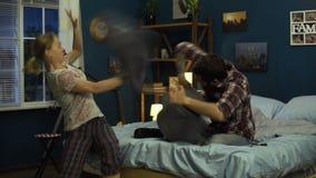 Couples riants combattant avec des oreillers sur le lit banque de vidéos