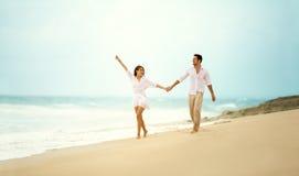 Couples riants dans l'amour tenant la main sur la plage Photos stock
