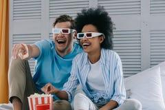 Couples riants en verres d'anaglyphe observant le film à la maison images stock