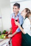 Couples riants faisant cuire dans la cuisine Photographie stock