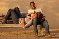 Couples riants se reposant sur le banc de parc dehors photo stock