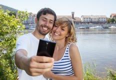 Couples riants sur la rivière prenant un selfie Image stock
