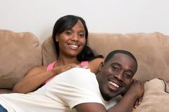 Couples riants sur une fin de divan vers le haut-Horizontale image stock
