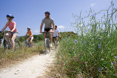 Couples riding bicycles on rural path stock photo