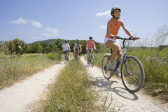 Couples riding bicycles on rural path royalty free stock images