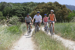 Couples riding bicycles on rural path stock photography